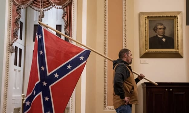 Unmasked rioter carries Confederate flag into White House