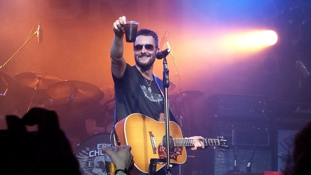 Eric Church raising his glass on stage from Whiskey RIff