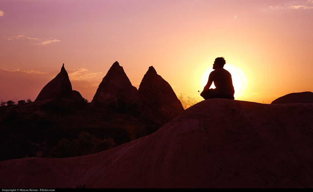 Man meditating on mountain top in sunset