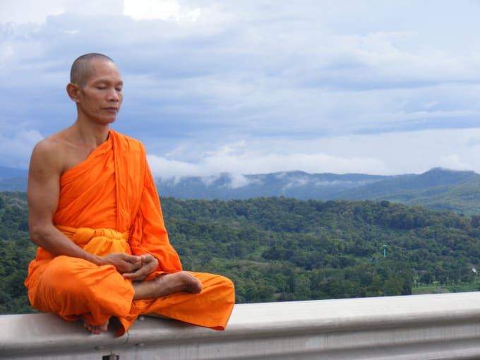 Monk meditating in front of mountain view