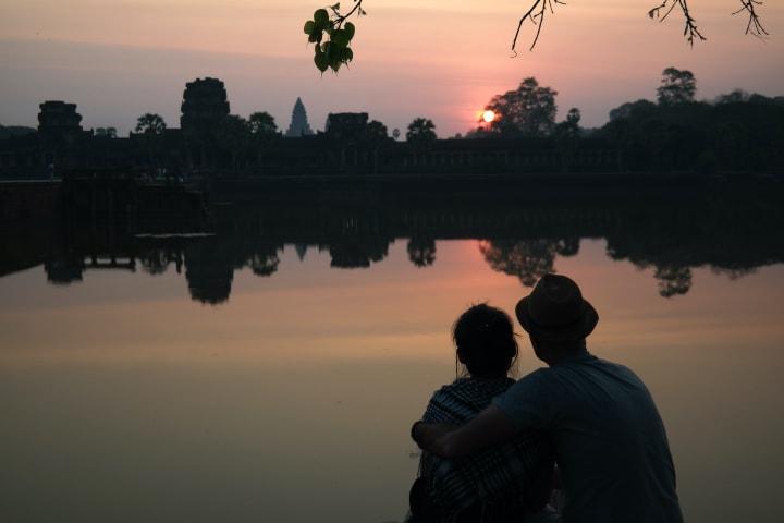 couple watching sunset at angkor wat temple
