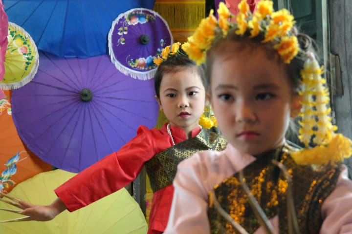 children performing at a street festival in Thailand