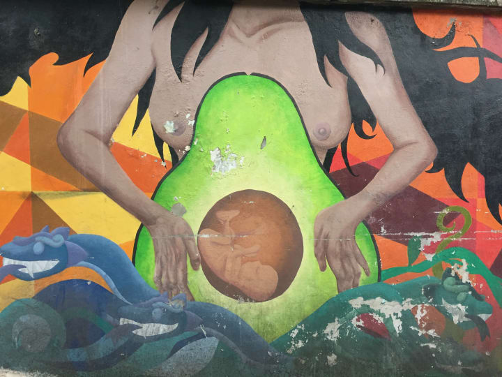 street art graffiti of a pregnant woman with avocado belly