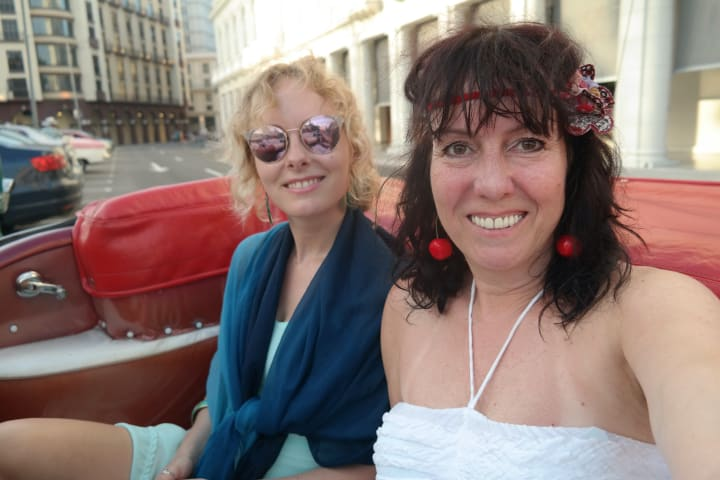 mother and daughter in a cuban car smiling