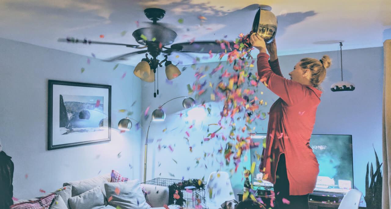 Chelsea dumping confetti into her ceiling fan.