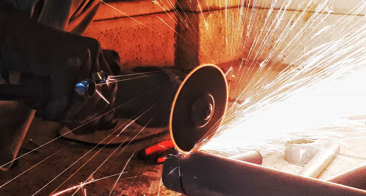 Sparks flying off a grinder being used to cut through a pipe.