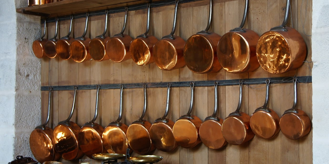 21 copper pots and pans hanging on a wall.
