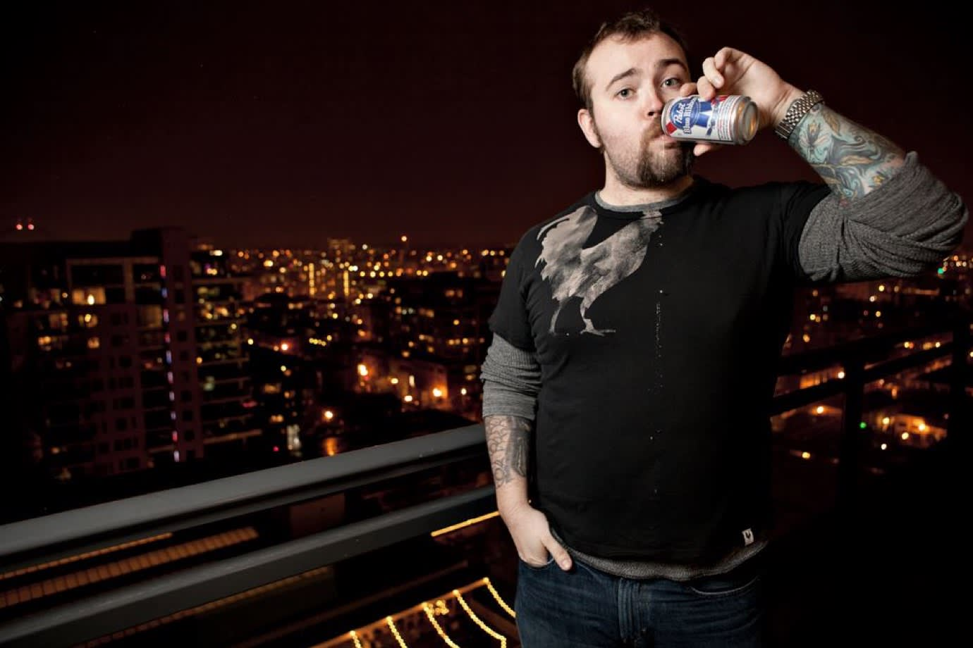 Jason Lengstorf on a balcony at night drinking beer.