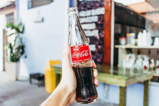 A hand holding a Coca-Cola. Photo by Talles Alves on Unsplash.