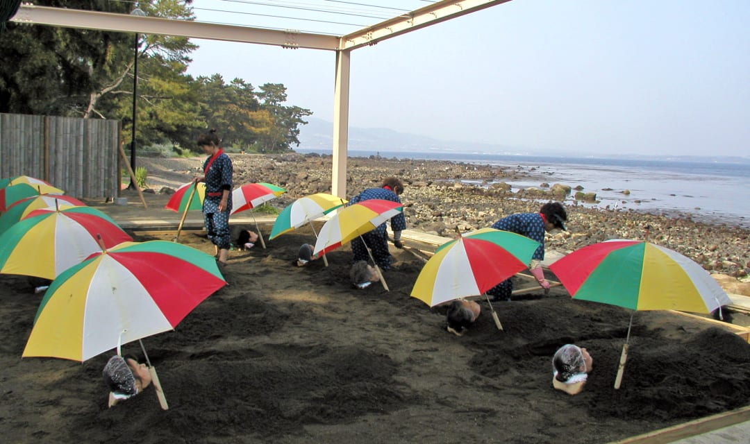 a group of women lie buried on beach under umbrellas