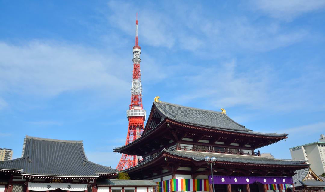 A temple roof with a red and white tower behind it