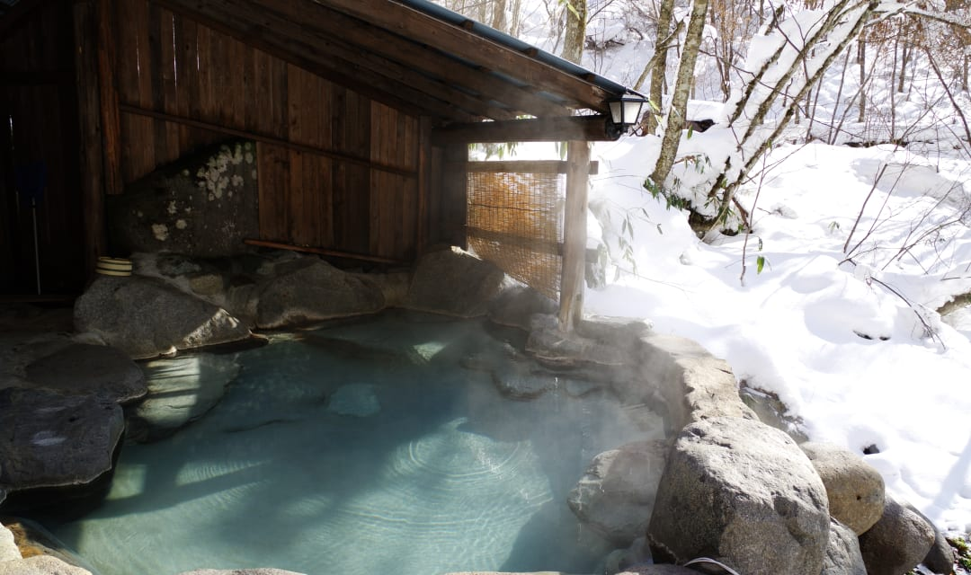 a blue outdoor onsen surorunded by rocks and snow outside a wooden structure
