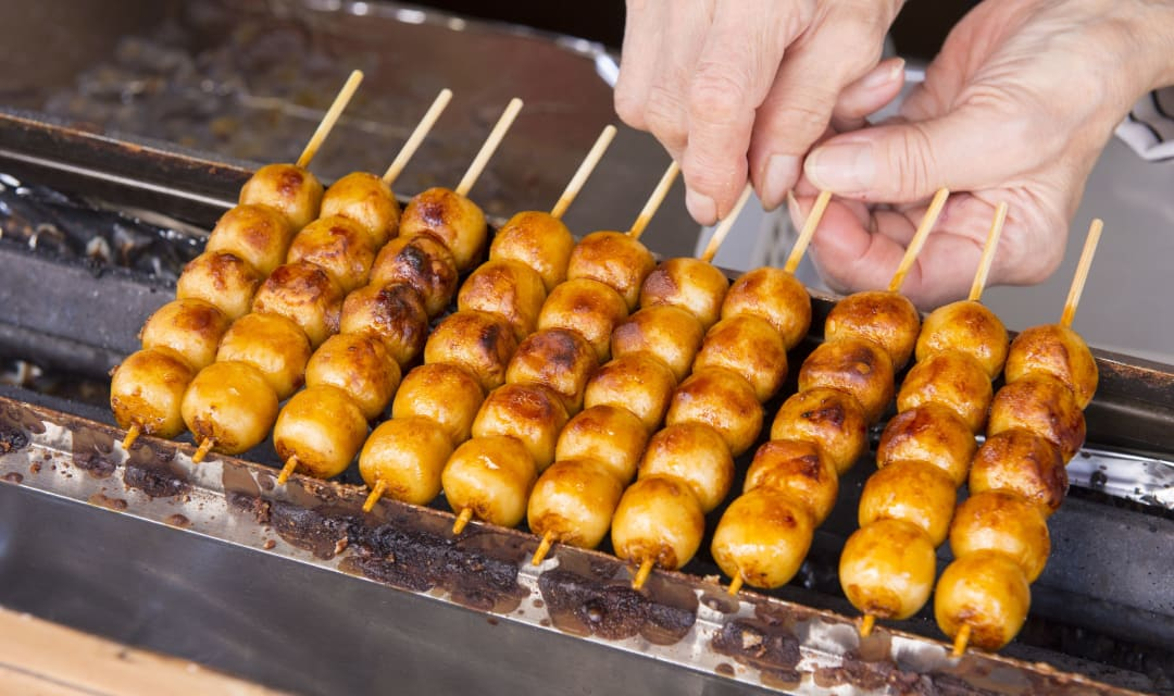 a griddle toasting mochi balls on sticks held by hands