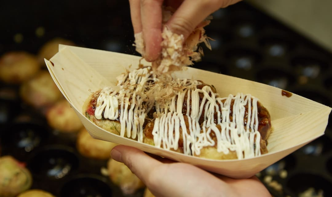 hands picking up takoyaki in a bowl