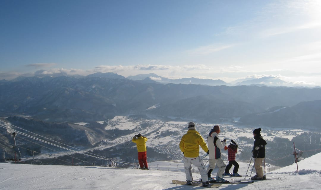 a group of skiers standing on top of a snowy mountain on a sunny day