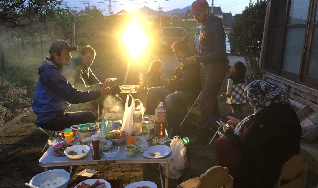 A group of people eat simple food as the sun sets