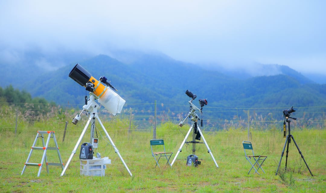 telescopes on a field with misty mountains in the background