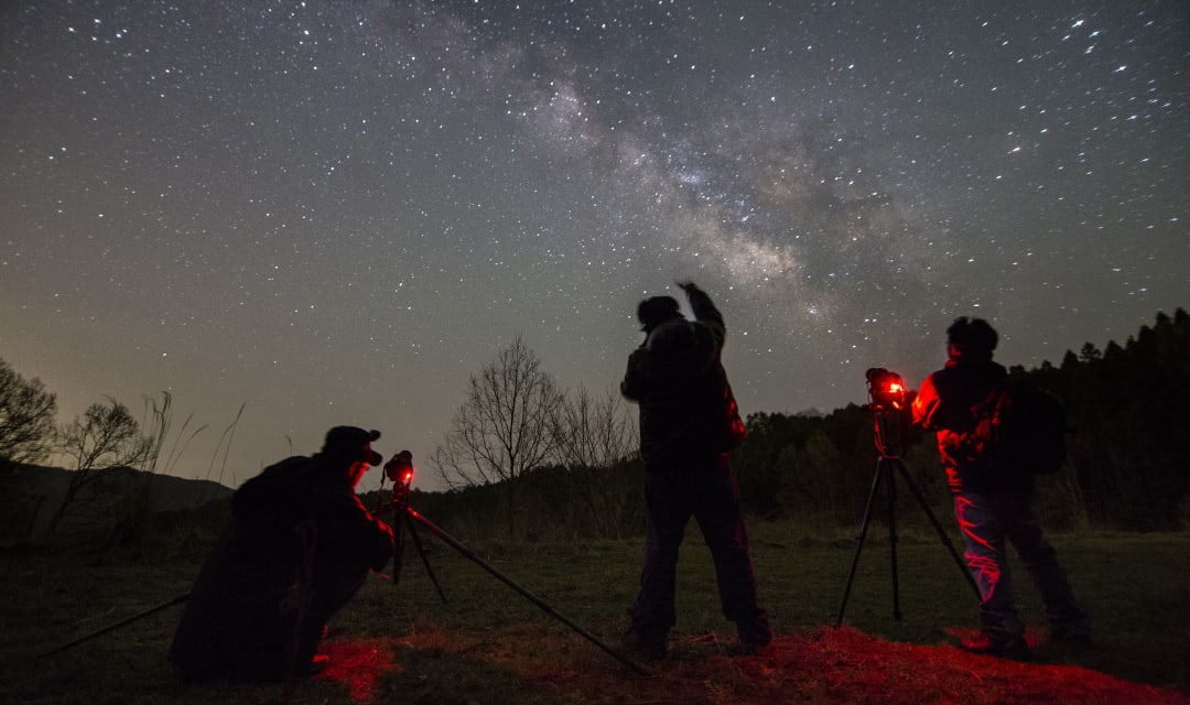silhouettes of three people standing outside at night looking at the milky way