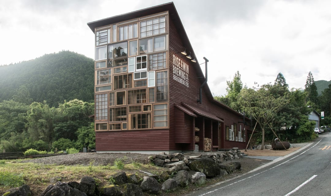 A wooden and glass building surrounded by mountains and nature