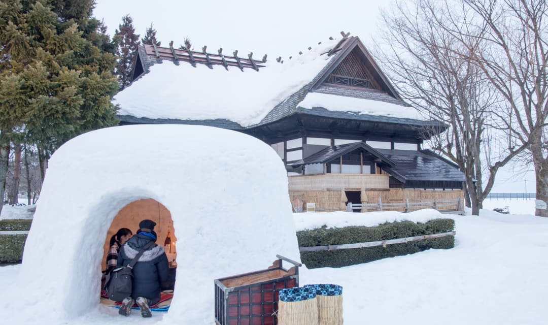 people inside a kamakura igloo next to a house on snowy ground