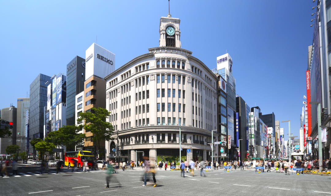 A city street in front of a large building with a clock on the top