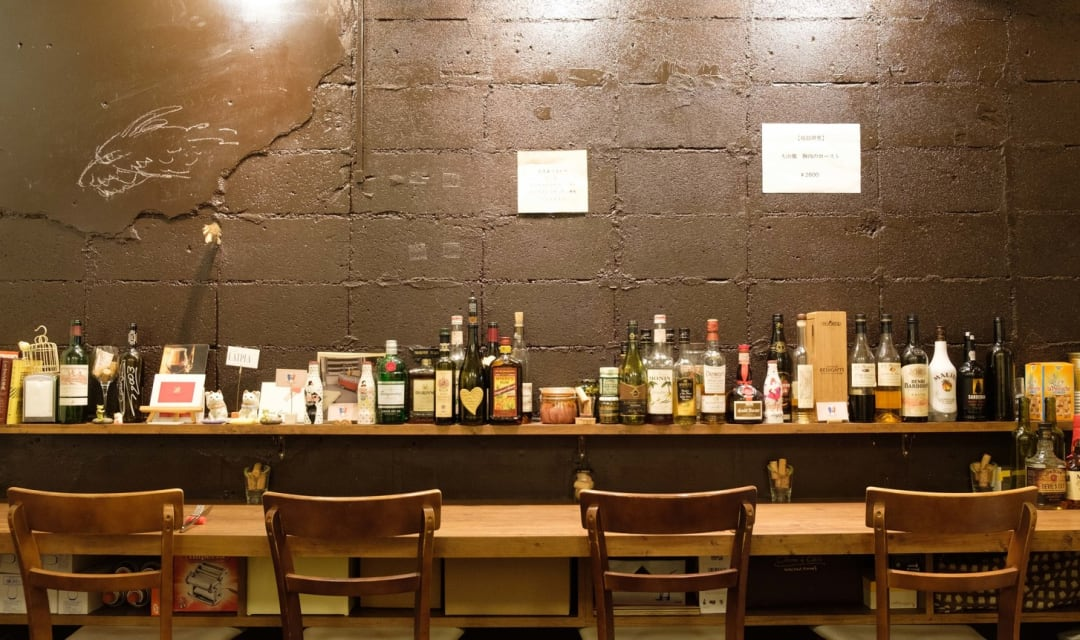 a row of chairs and a counter table behind a shelf with bottles of alcohol