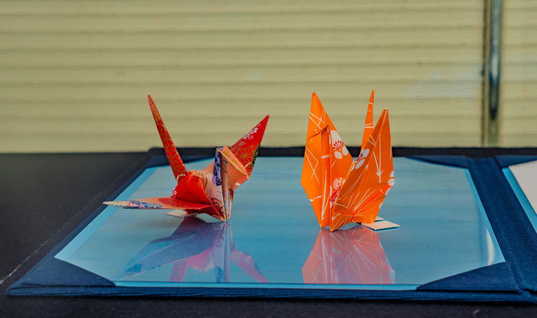 two colorful folded paper birds on a table