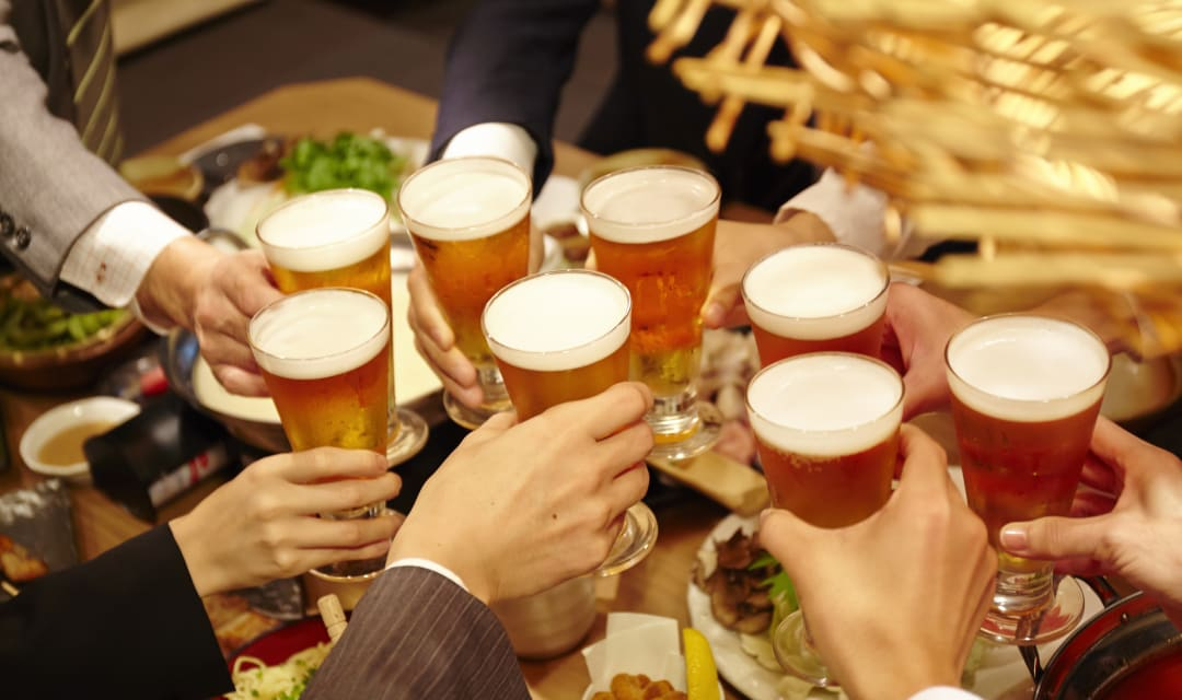 eight glasses of beer held by hands above food on a table