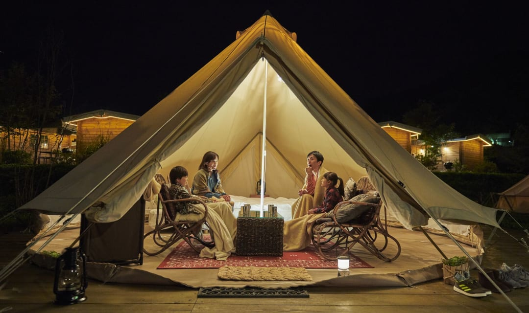 four people sitting in an open, lit tipi at night