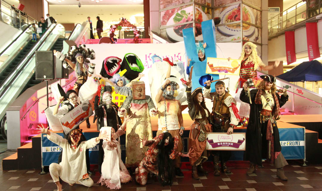 people in halloween costume posing in a shopping mall