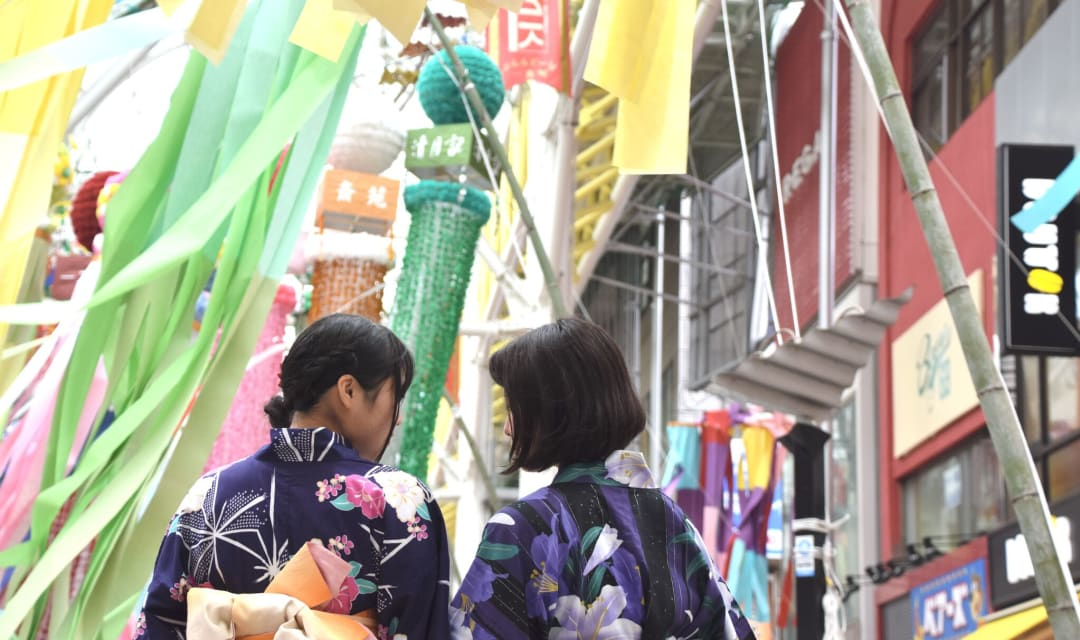 the back of two women in yakata standing in front of festive streamers on a street