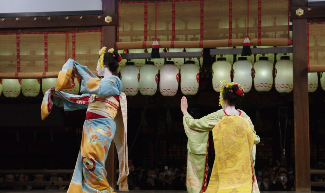 Two geisha dancing on a stage decorated with lanterns