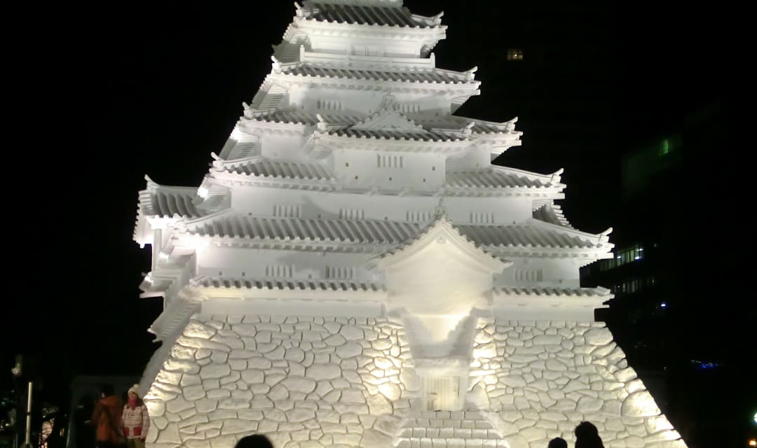 a japanese castle made from ice lit up at night