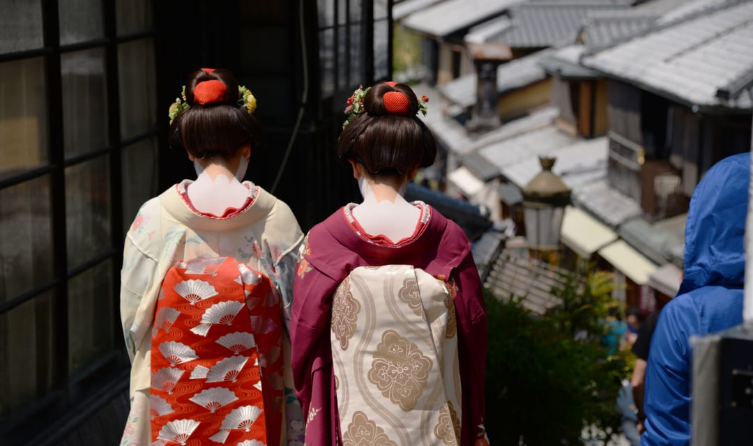 backs of two women in kimono walking along a traditional street