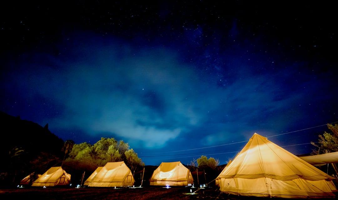 a row of tipis at night