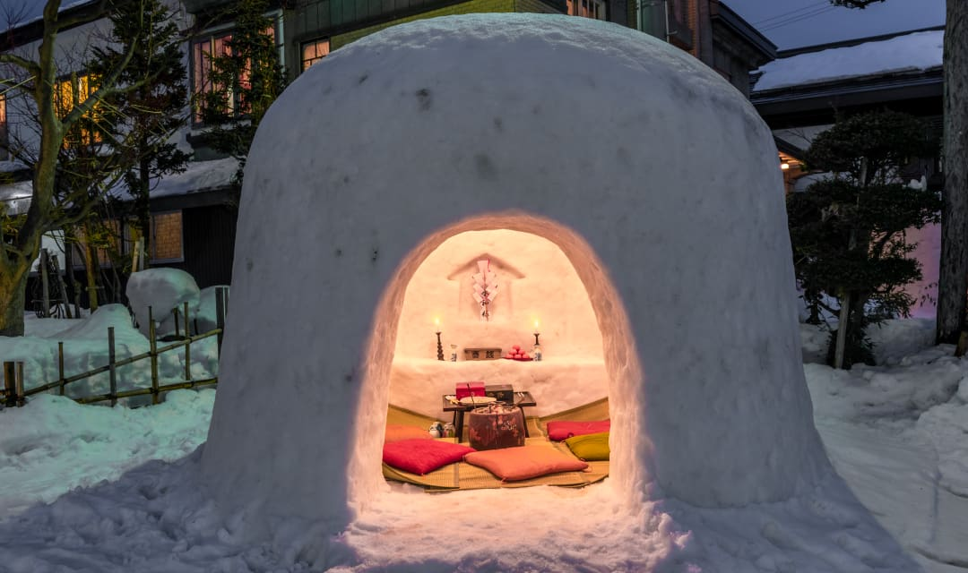 cushions and candles inside a kamakura igloo on the snowy ground on a dark night