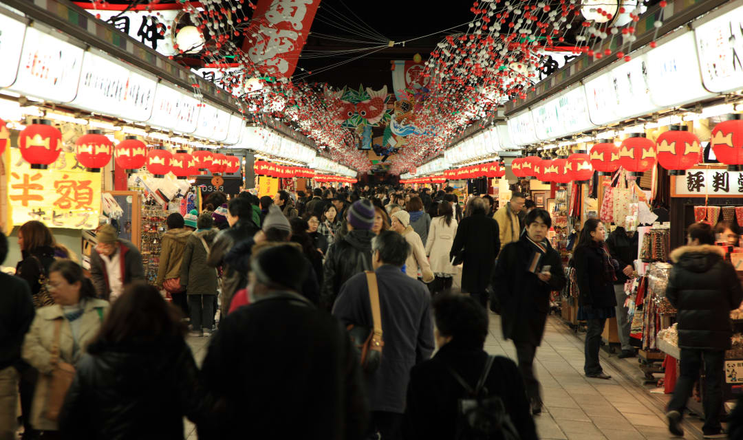 a path lined with shops full of people shopping at night