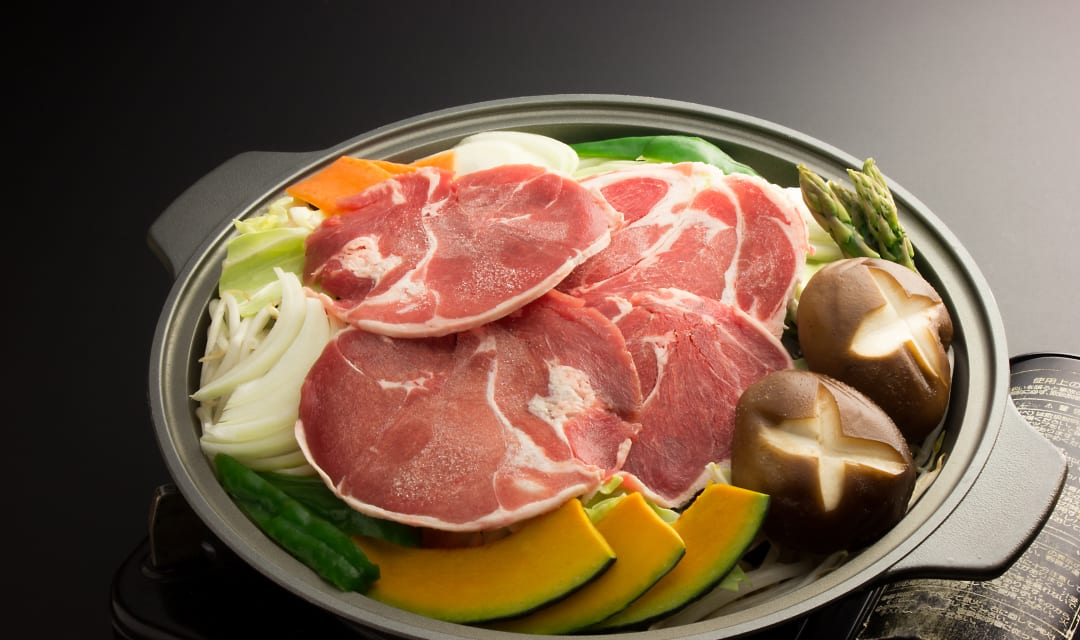 a pan full of raw meat and vegetables on a grey bancground