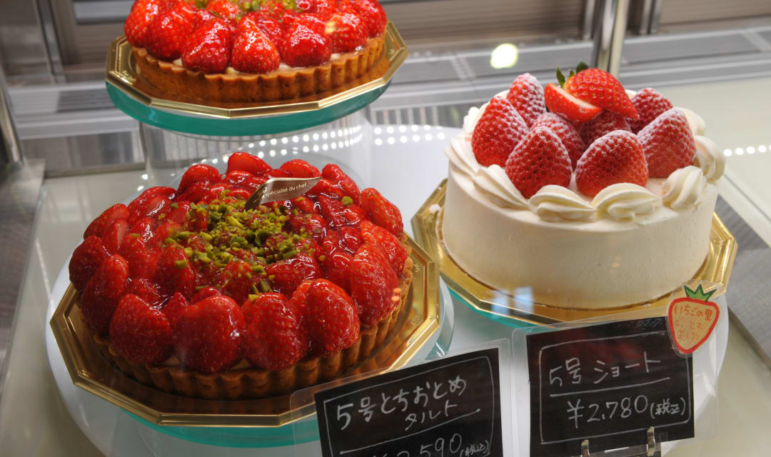 three strawberry and cream cakes and tarts in a fridge