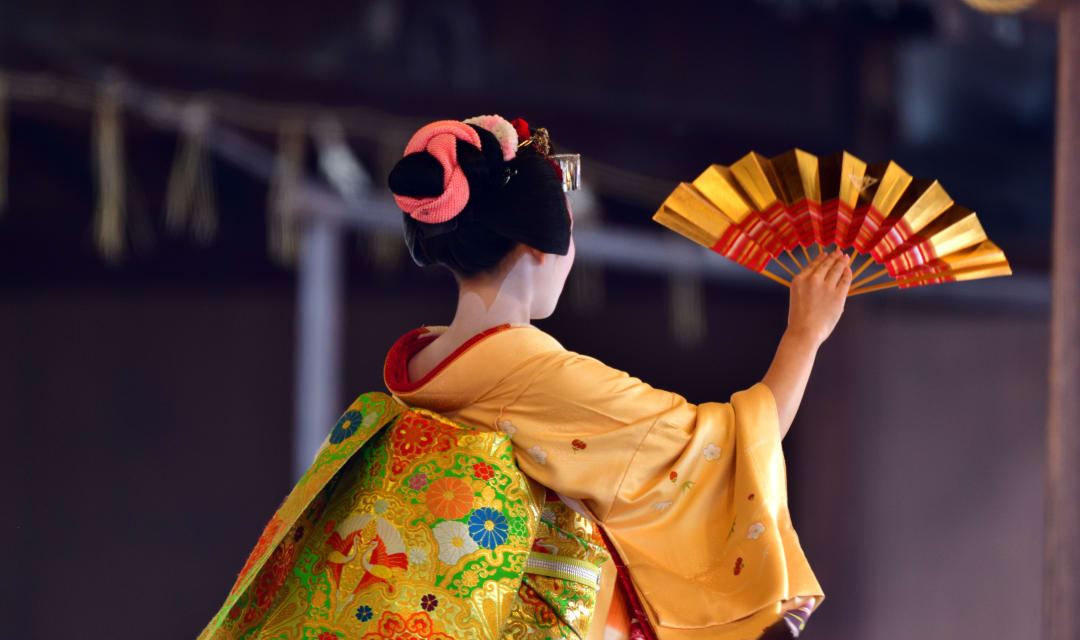 Back of a woman wearing a yellow kimono and holding a fan