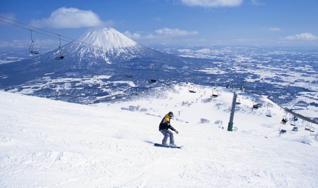 a person skiing with a ski lift and snowy mountain in the background