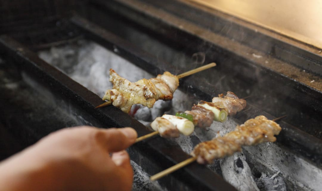 yakitori chicken and leeks being grilled on coals