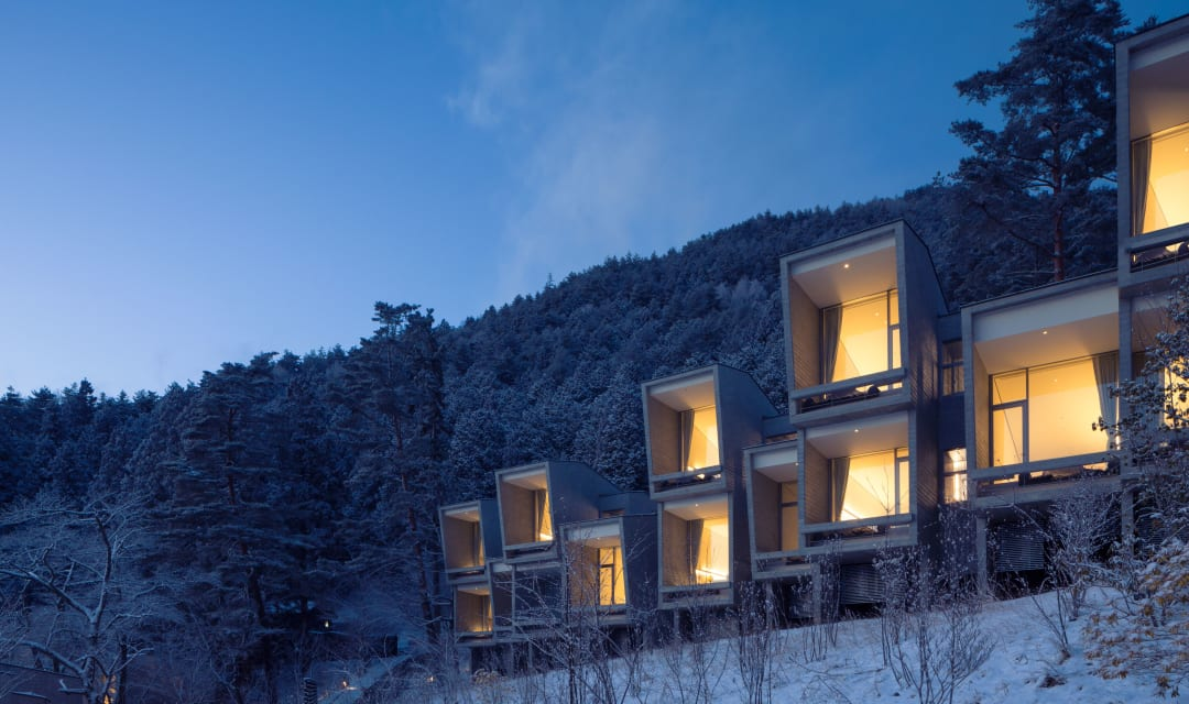 stacked square lit-up cabins on a snowy mountainside at night