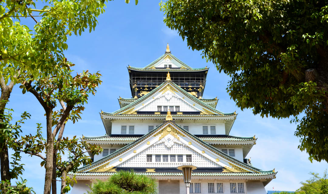Japanese Castle against a blue sky, with trees either side of it
