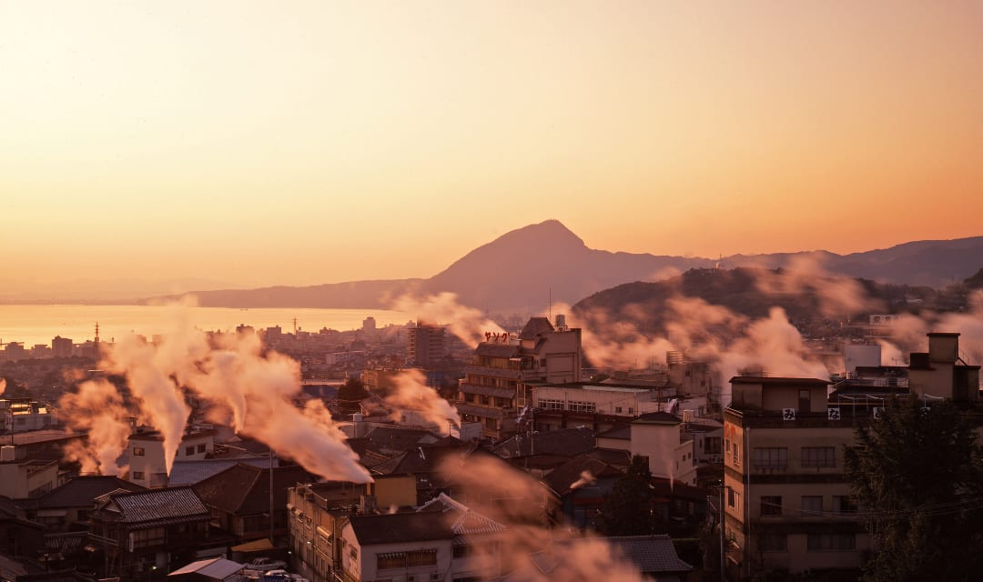 A townscape with mountain backdrop and steaming onsens