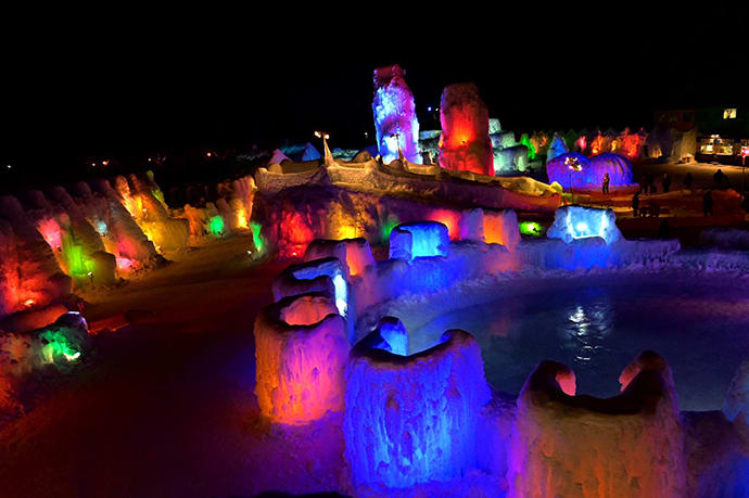 Multicolored lights illuminate the sculptures at night.