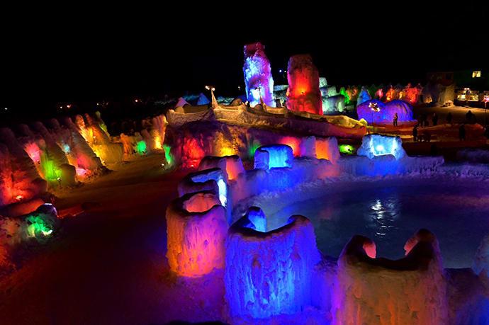 Multicolored lights illuminate the sculptures at night.