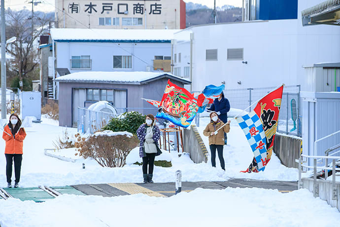 Passengers are welcomed with fishermen's banners as the train approaches Kuji Station.