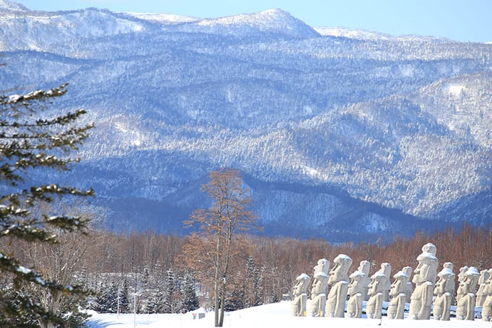 Snow covers the Moai statues and surrounding mountains in winter. Photo credit: Makomanai Takino Cemetery