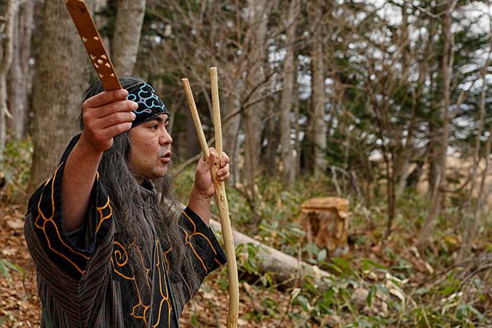 Ainu guide Kengo Takiguchi holds a ritual offering stick (ikupasuy) in his right hand.